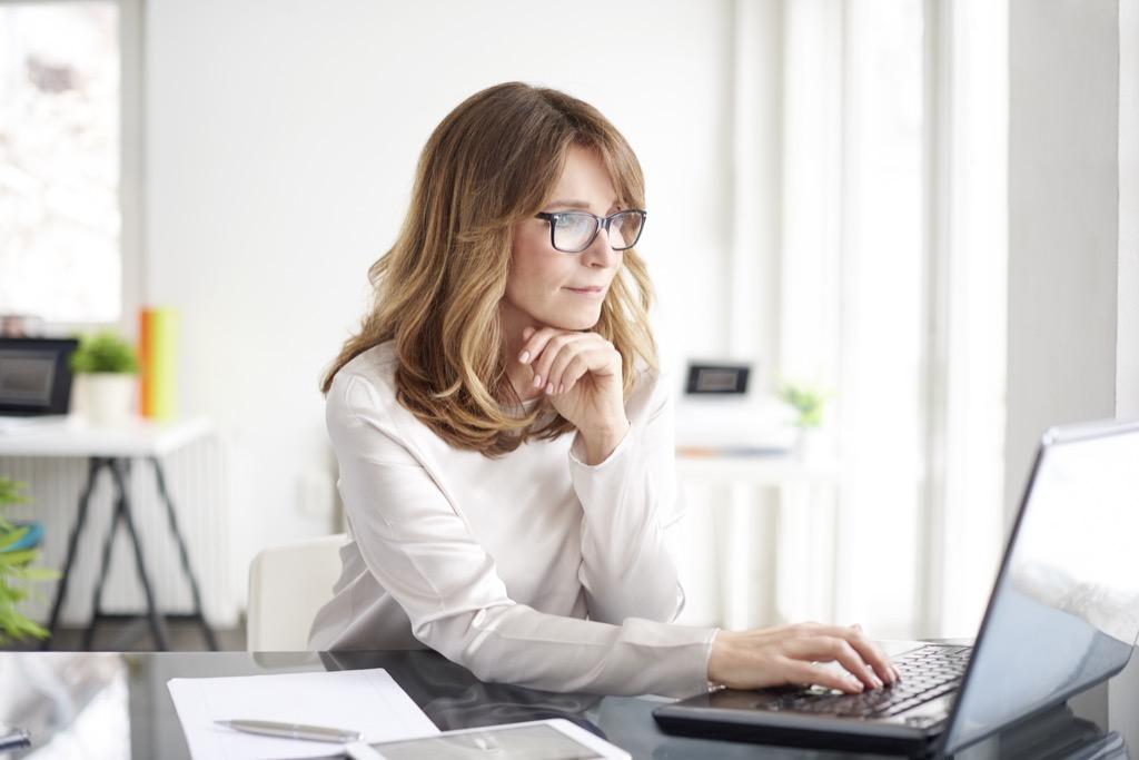Kobieta szuka na komputerze kodu rabatowego obniżającego cenę podpisu elektronicznego